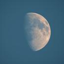 Gibbous moon in blue sky,                                Steed Yu